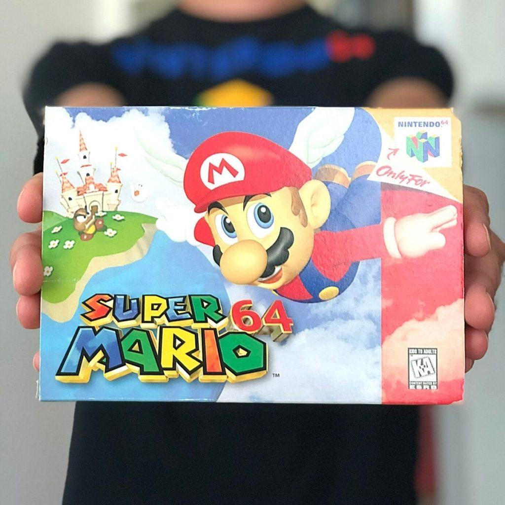 A person holding a Super Mario 64 game box.