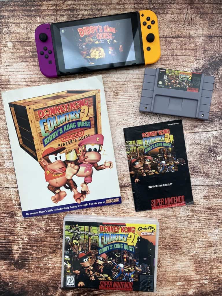 Donkey Kong Country 2 Cartridge, Box, Player's Guide and Nintendo Switch playing DKC 2
