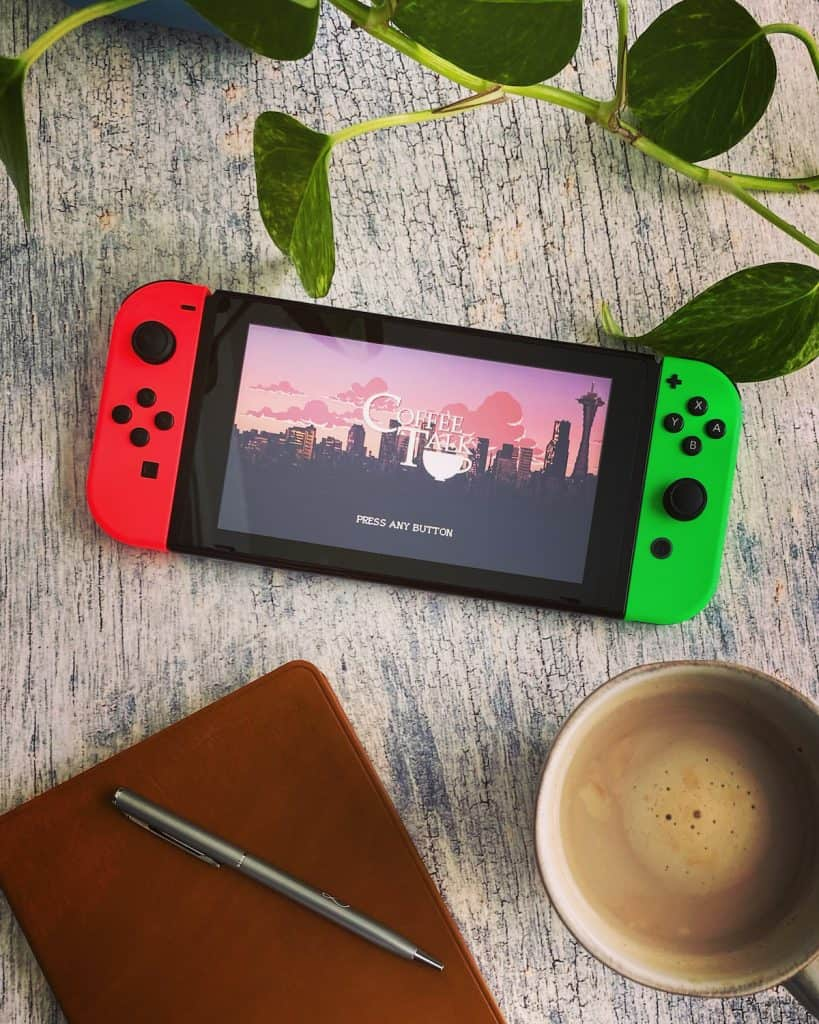 Nintendo Switch playing Coffee Talk with coffee mug, notebook, and plant nearby