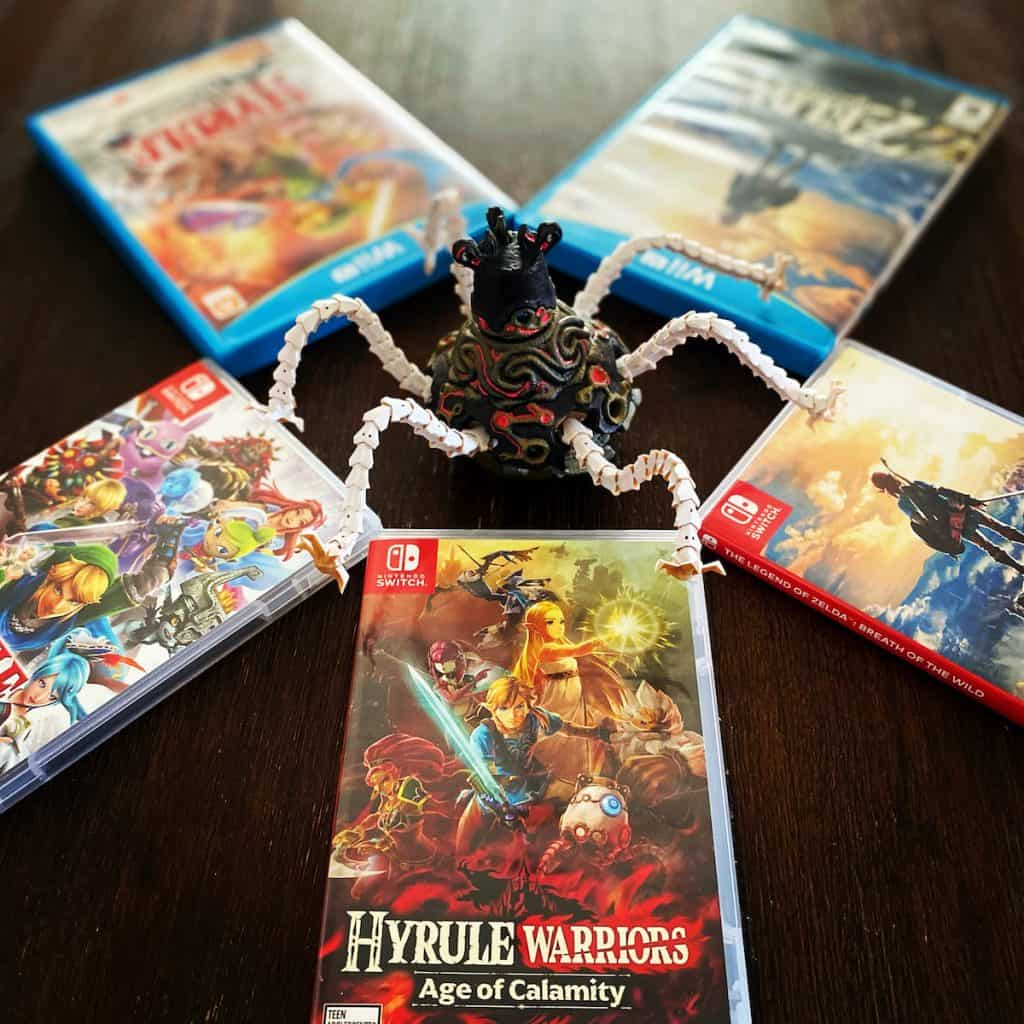 Hyrule Warriors Age of Calamity box with Guardian amiibo and previous Zelda games