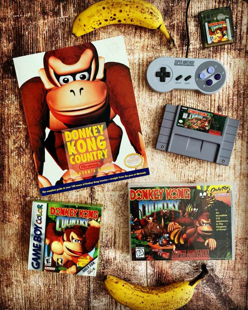 Donkey Kong Country SNES cart, player's guide, Game Boy Color box, Super Nintendo controller, and bananas