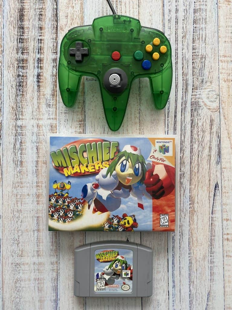 Mischief Makers cart, box art, and jungle green N64 controller