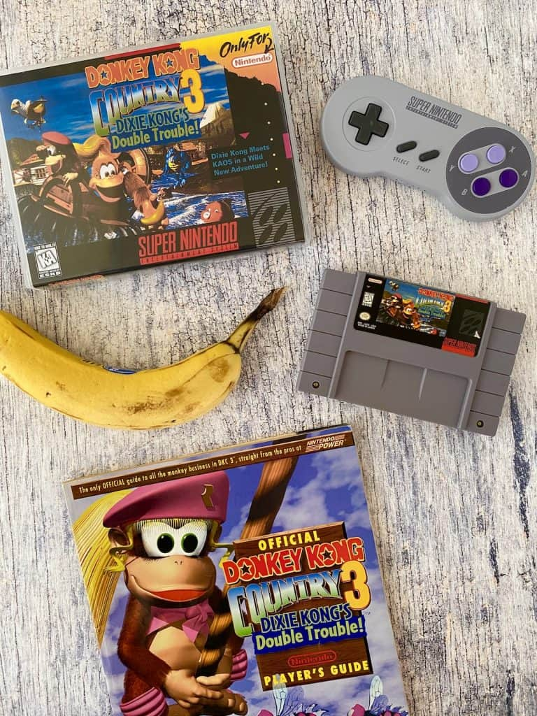 Donkey Kong Country 3 box, cart, player's guide, SNES controller, and banana