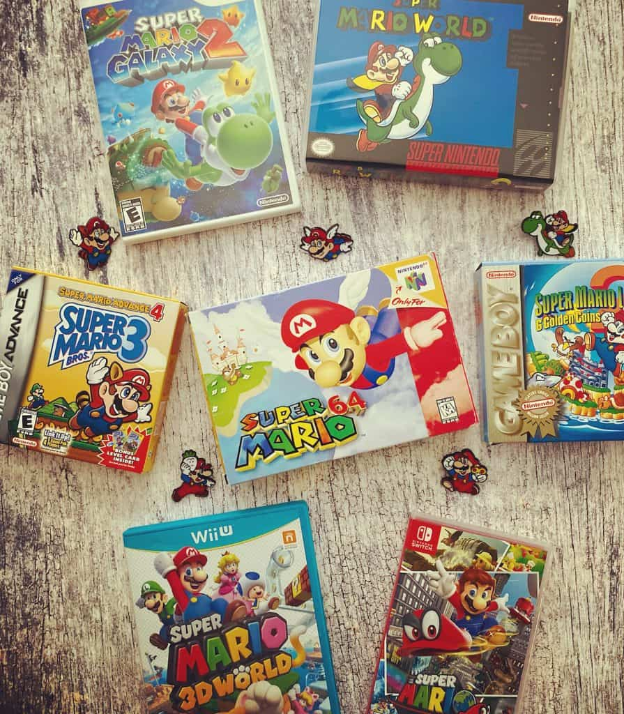 Box art of Mario 64, Super Mario World, Super Mario Bros 3, Super Mario Galaxy 2, Super Mario 3D World on Wii U, Super Mario Odyssey, and Super Mario Land 2: Six Golden Coins with Mario anniversary pins