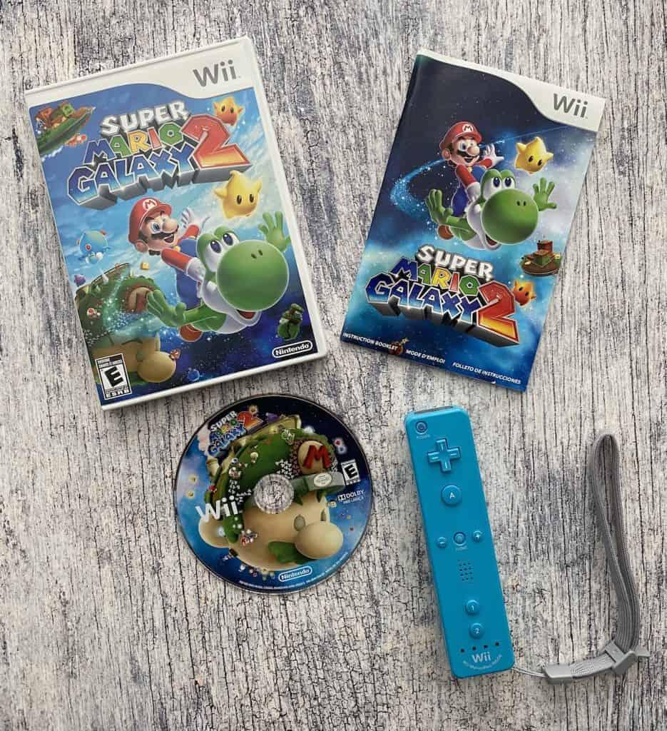 Super Mario Galaxy 2 box art, manual, disc, and blue wii remote