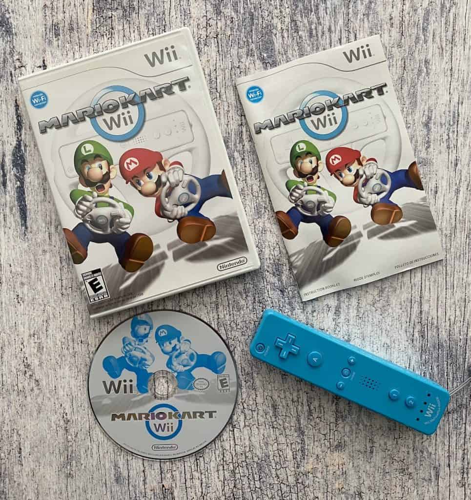 Mario Kart Wii case, disc, manual, and blue Wii remote