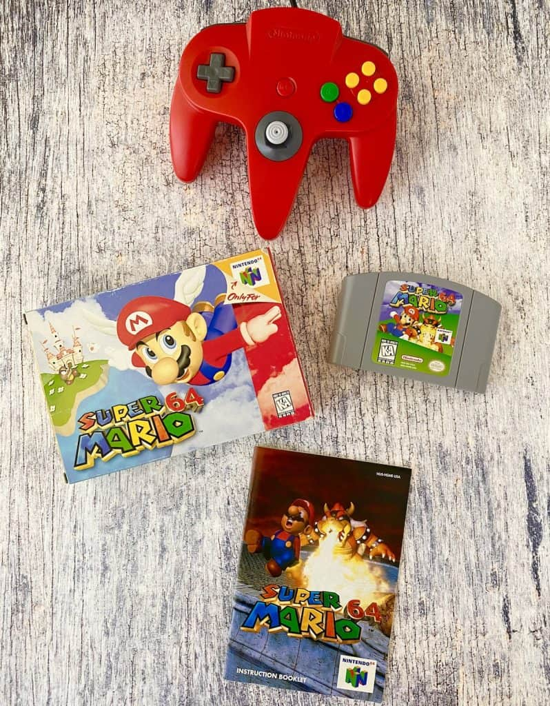Super Mario 64 box, cart, manual, and red N64 controller