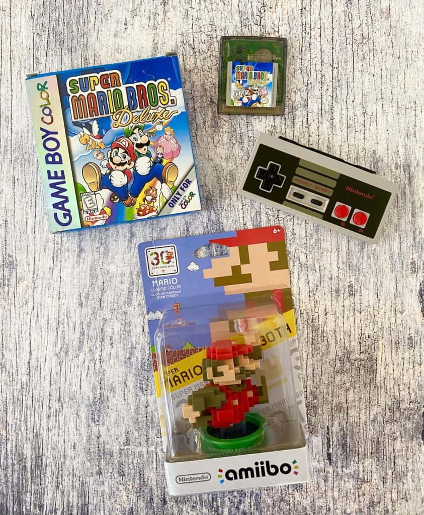 Super Mario Bros Deluxe for Game Boy Color box, cart, NES controller, and Mario 30th anniversary classic amiibo
