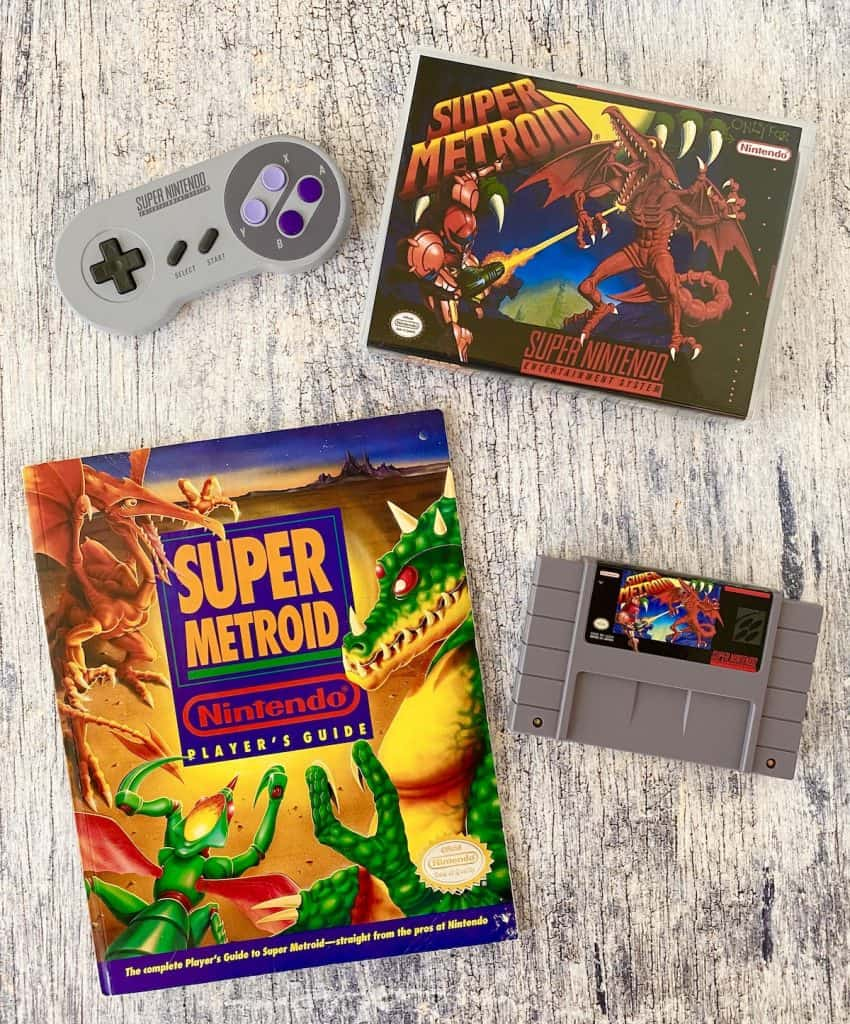 Super Metroid box, cart, Nintendo Power player's guide, and SNES controller