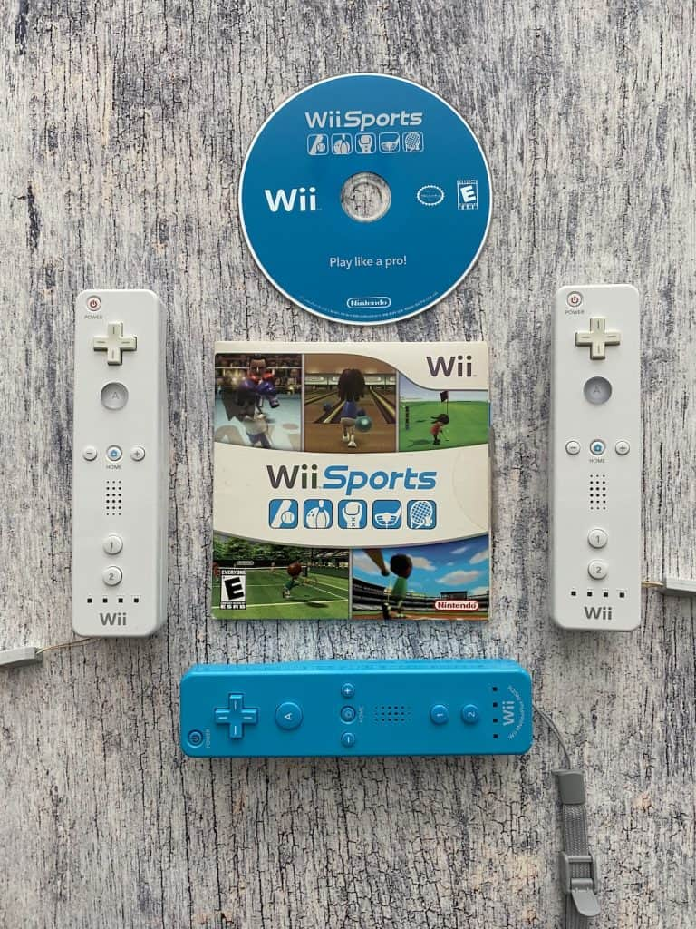 Wii sports case, disc, and three Wii remotes