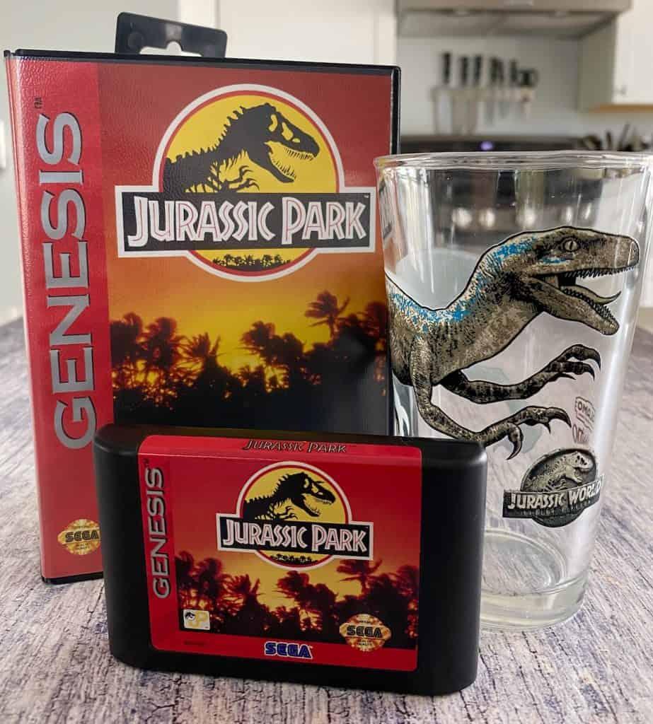 Jurassic Park Sega Genesis box, cart, and raptor pint glass