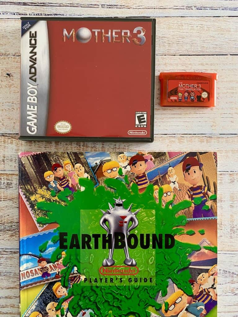 Mother 3 box art, fan translation cart, and Earthbound Player's Guide