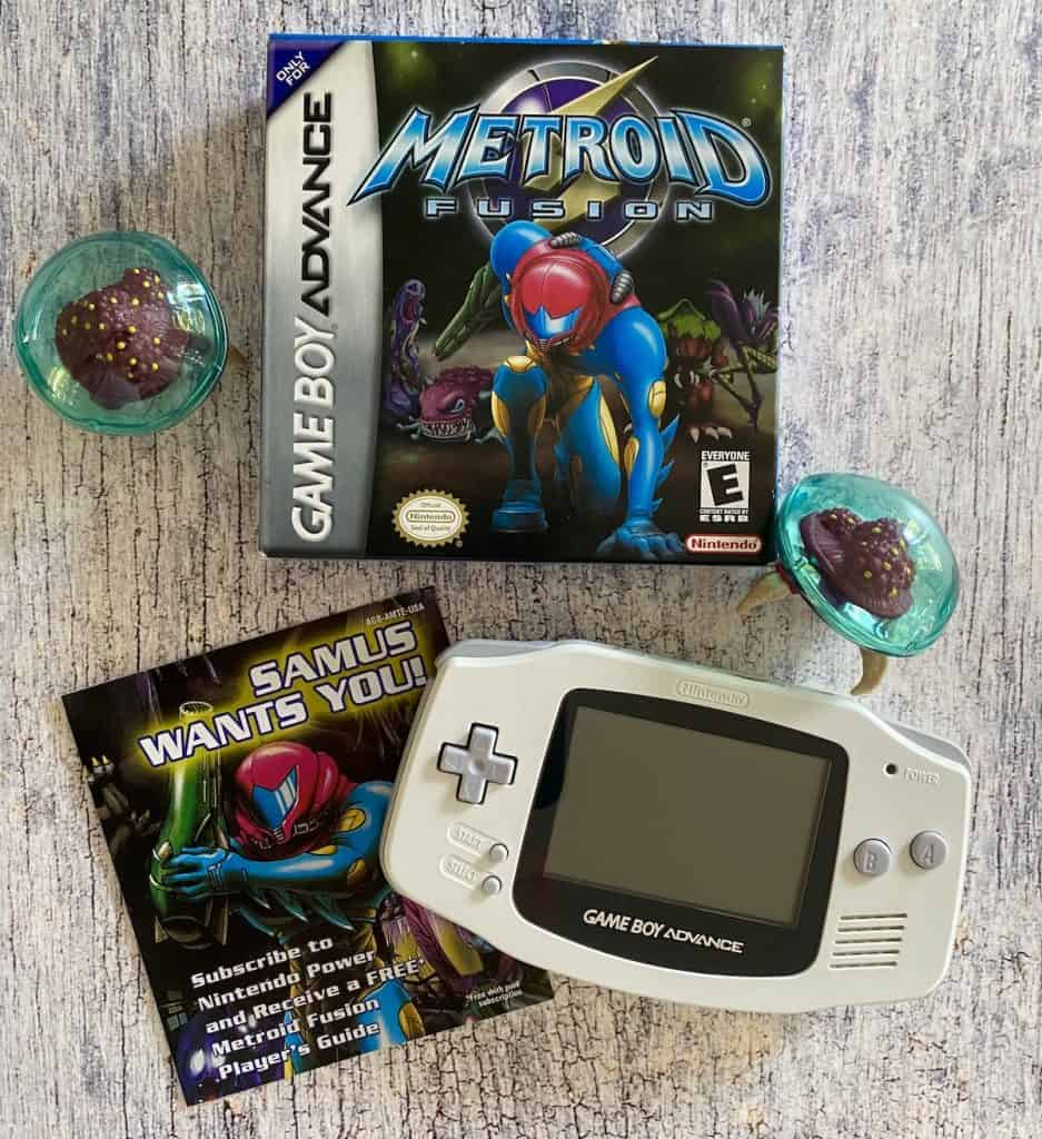 Metroid Fusion box and insert, white Game Boy Advance, and two Metroid figures