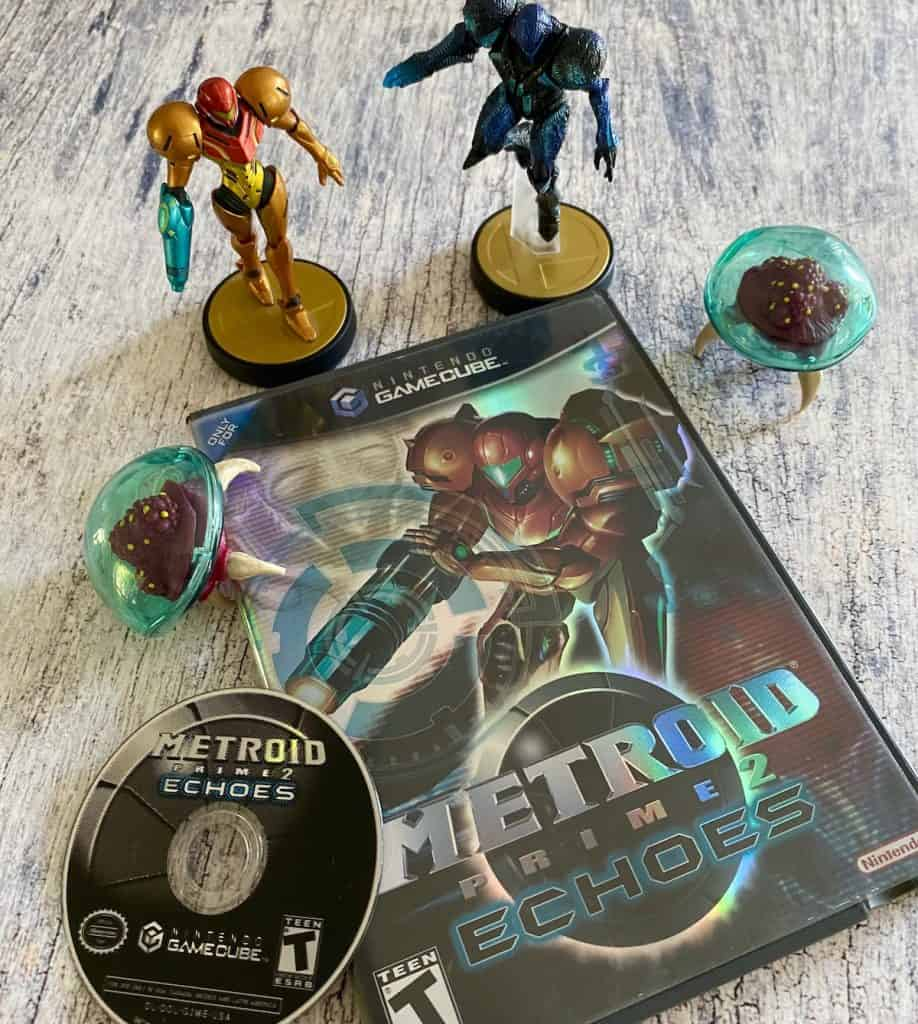 Metroid Prime 2 Echoes case and disc, with Samus and Dark Samus amiibo and two Metroid figures