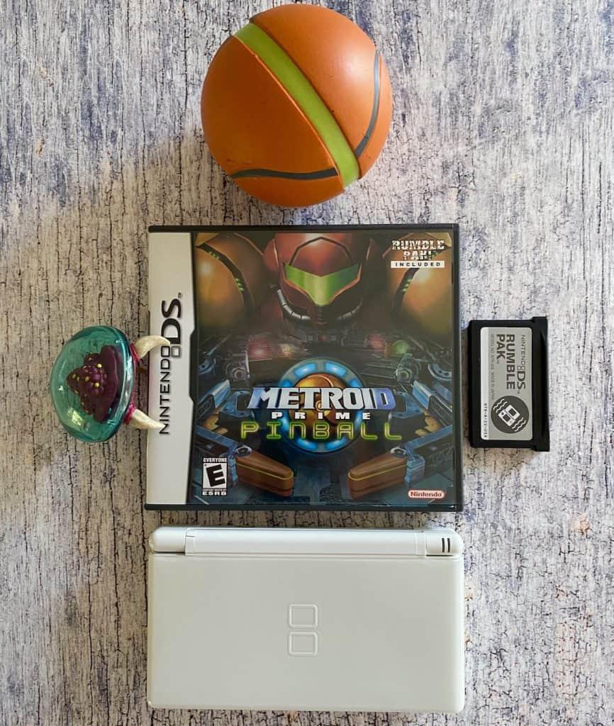 Metroid Prime Pinball case, DS lite, GBA Rumble Pak, Metroid figure, and Morph Ball stress ball