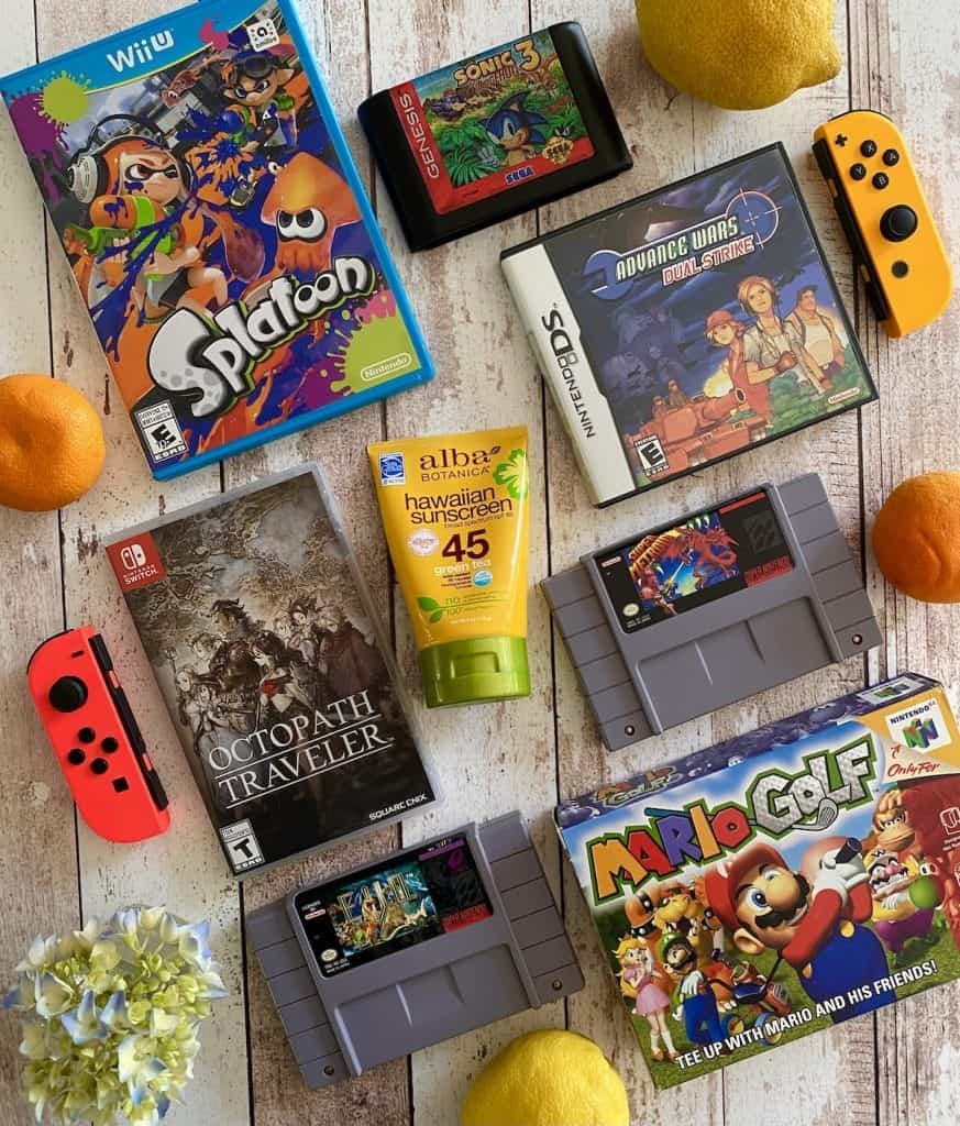 Collage of games I play during the summer-Splatoon, Sonic 3, Advance Wars Dual Strike, Octopath Traveler, Super Metroid, Mario Golf, EVO Search for Eden, with summer items around (lemons, oranges, sunscreen, flowers)