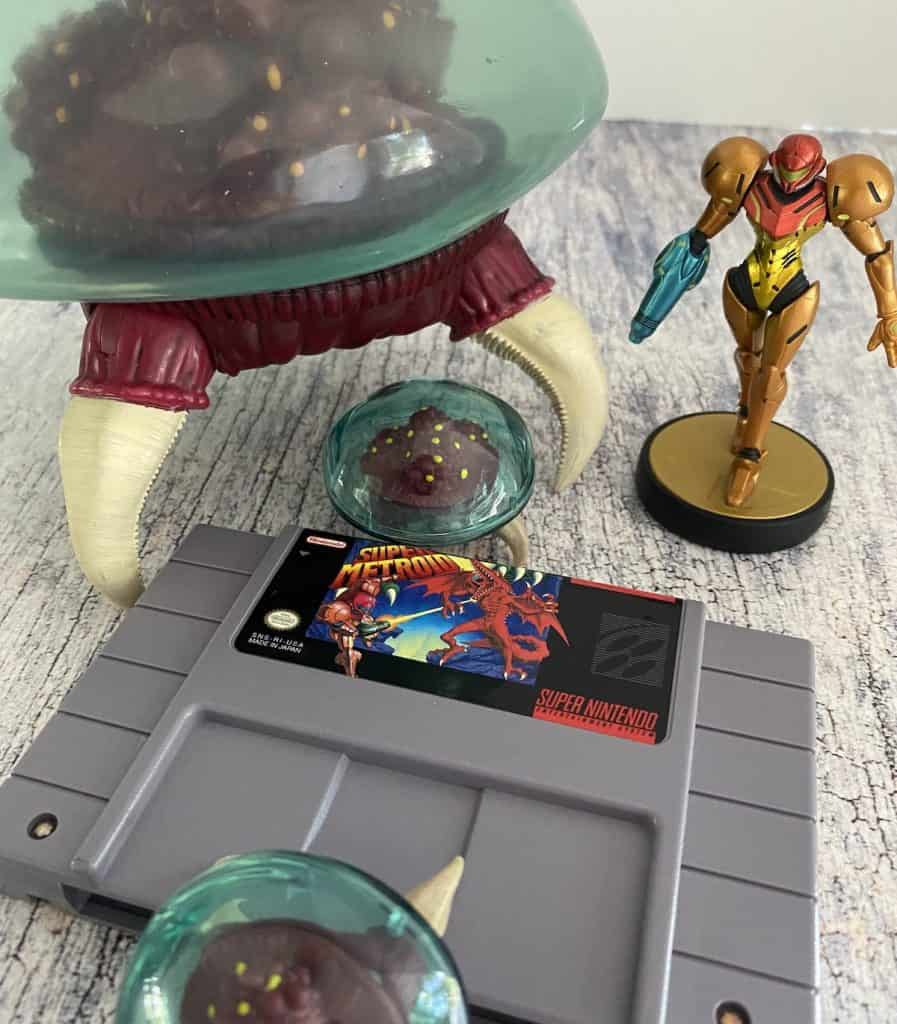 Super Metroid cart with big Metroid figure, two small Metroid figures, and Samus amiibo