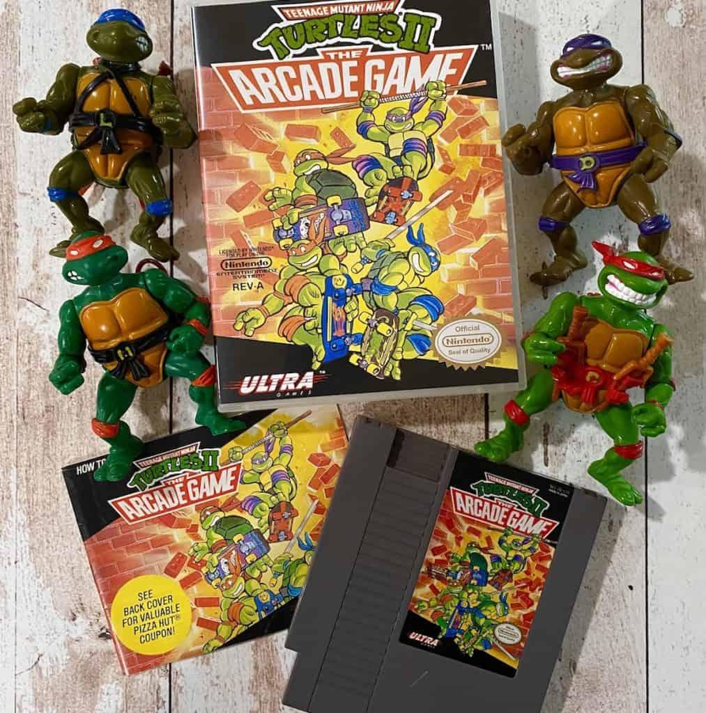 Turtles II Arcade Game NES cart, box, manual, and action figures of Leonardo, Donatello, Rafael, and Michaelangelo