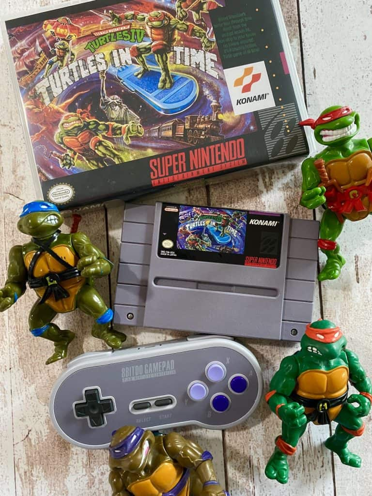 Turtles in Time SNES box, cart, 8bitdo SNES controller, and action figures for Leonardo, Donatello, Raphael, and Michaelangelo