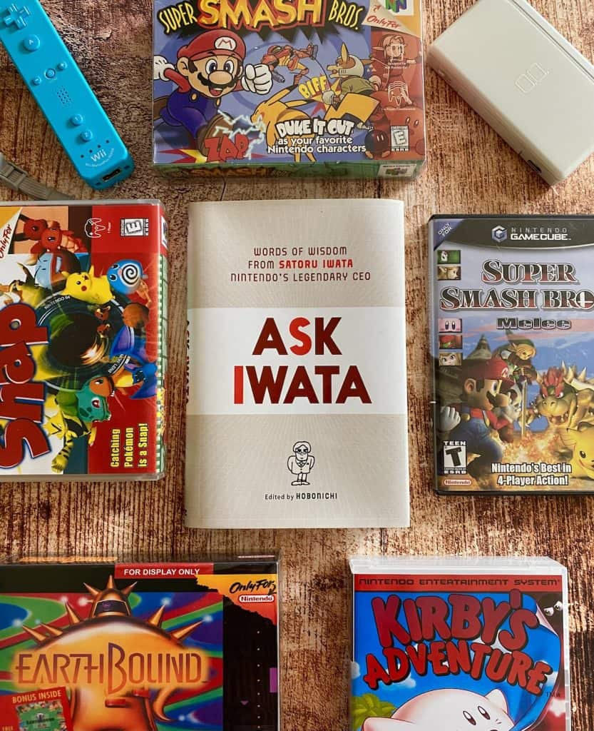 Ask Iwata Book with Wii remote, Nintendo DS, Super Smash Bros. N64, Pokemon Snap, Smash Melee, Earthbound, and Kirby's Adventure