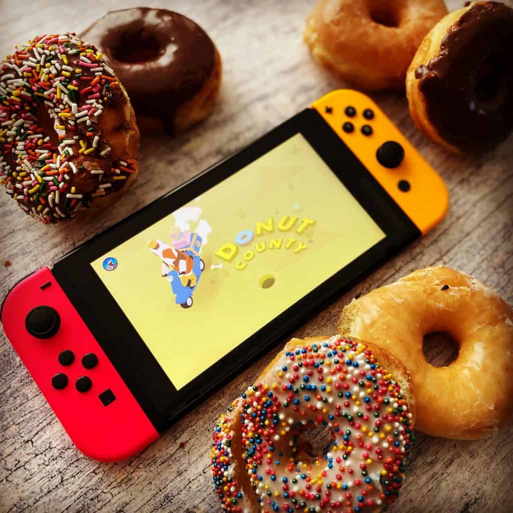 Donut County on Switch surrounded by actual donuts