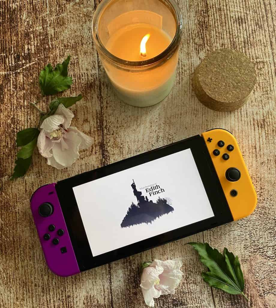 What Remains of Edith Finch title screen on Switch, surrounded by a lit candle and fallen leaves