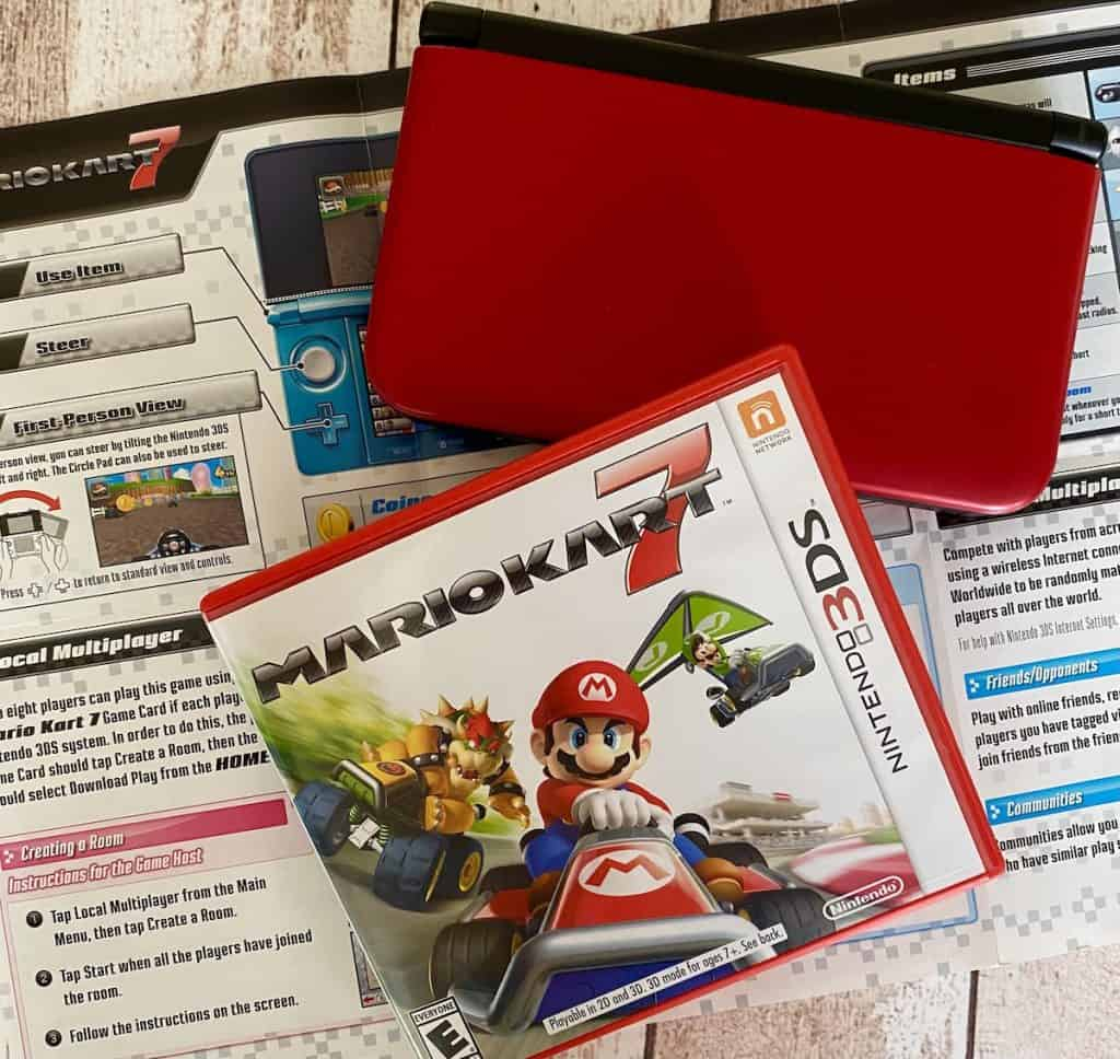 Mario Kart 7 box, fold out manual, and Red Nintendo 3DS XL